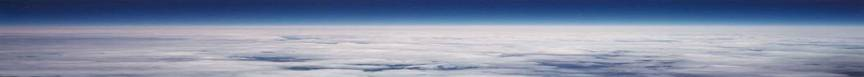 The horizon with blue skies and white clouds over the earth below